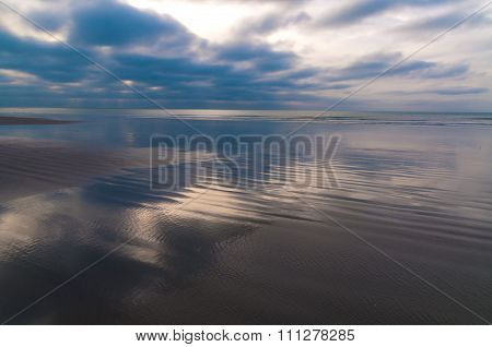 Dramatic Cloudscape Reflecting On Coastline In Cote D'opale In France At Dawn