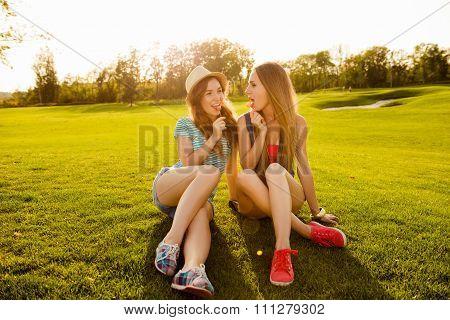 Two Slender Girls Licking Lollipops On The Grass