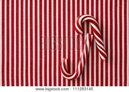 Peppermint candy canes on striped background