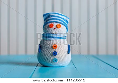 Snowman wearing striped sweater on blue wooden background, merry Christmas. With empty space for con
