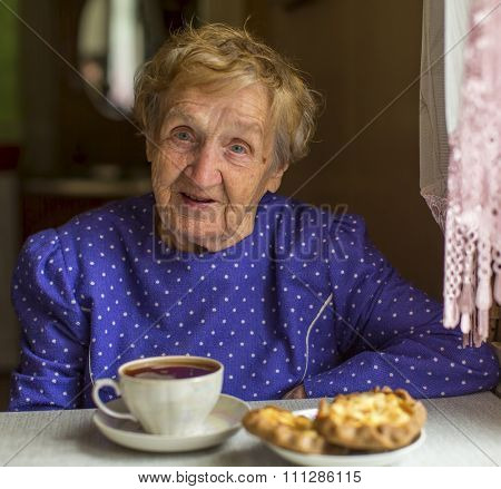 Elderly woman drinking tea with homemade cakes.