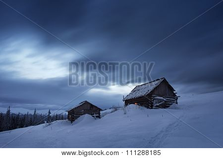 Night landscape. Winter in mountain village. Light in windows of wooden houses. Path in snow. Carpathians, Ukraine, Europe