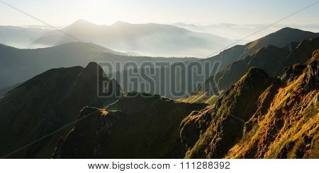 Mountain panorama. Beautiful backlight on the hills. Autumn landscape in the morning. Carpathians, Ukraine, Europe