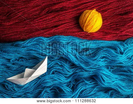 Cute white of origami boat floating on the waves of woolen thread towards the sunset