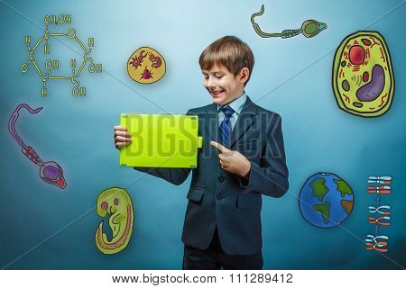 Teen boy businessman points his finger to the tablet and smiles
