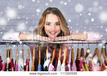 Beautiful young woman near rack with hangers  over snow effect