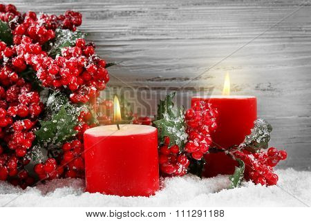 Candles and branch of holly berries in a snow over wooden background, still life