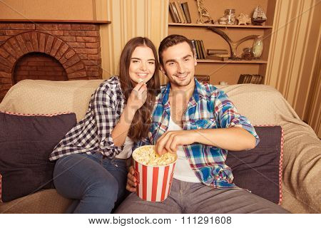 Young Beautiful Couple At Home Watching A Movie And Eating Popcorn