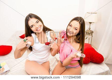 Beautiful Cheerful Girls In Pajamas Holding Varnishes