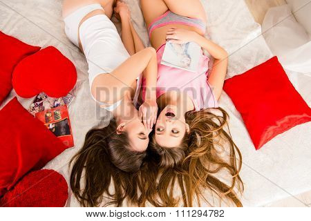 Surprised Girls In Pajamas Gossiping And Lying On The Bed Holding Magazines