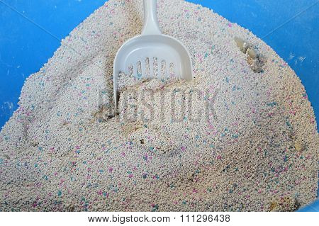 cat litter and dustpan in basin