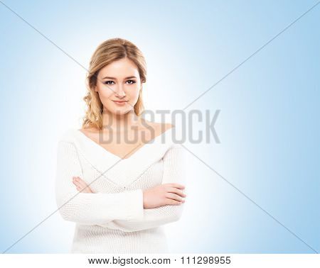Beautiful blond in white knitwear on blue background.