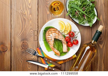Grilled salmon and white wine on wooden table. Top view with copy space