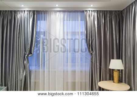 Table lamp by curtains in room