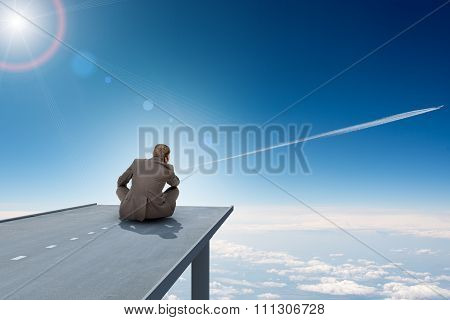 Businessman sitting on road with city