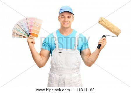 Young house decorator holding a color swatch and a paint roller isolated on white background