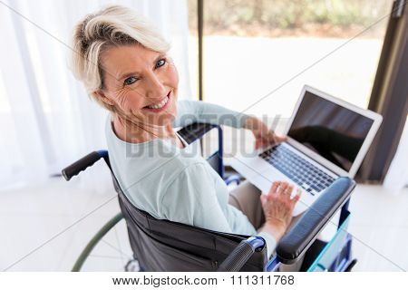 pretty disabled middle aged woman with laptop computer at home