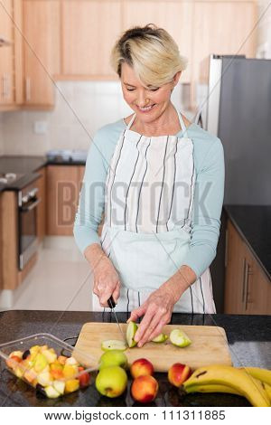 cheerful mid age woman making fruit salad in kitchen