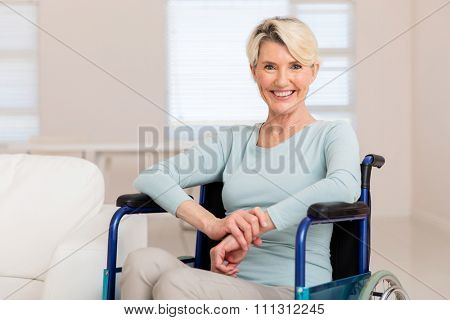 happy mid age woman sitting on wheelchair and recovering from sickness