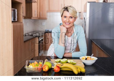 happy middle aged woman leaning against the kitchen counter