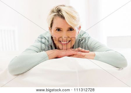 peaceful mid aged woman lying on bed at home