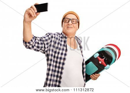 Senior skater holding a skateboard and taking a selfie with his cell phone isolated on white background