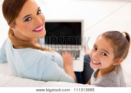 cheerful mother and daughter with laptop looking back