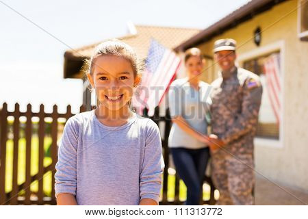 adorable little girl standing in front of parents outdoors