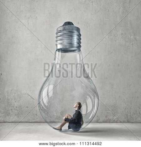 Young woman sitting inside of glass light bulb