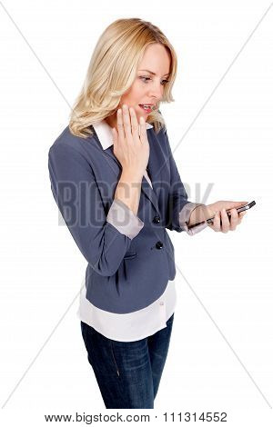 Young blonde woman staring at her mobile phone