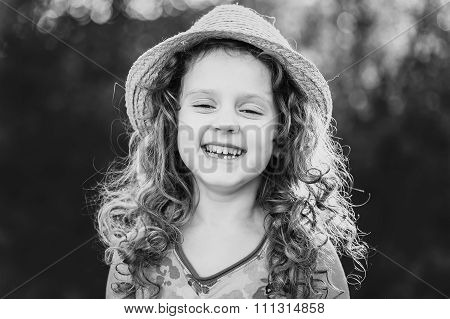 Black and white portrait of a funny little girl. Child missing tooth.