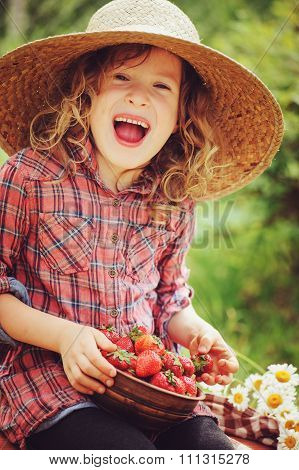 happy child girl in hat and plaid dress picking strawberries on sunny country walk in garden