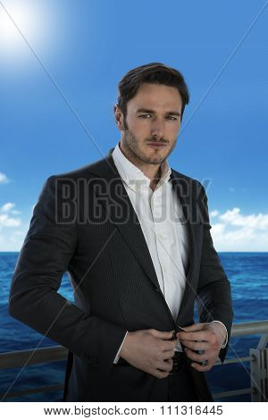 Young man against handrail on cruise ship