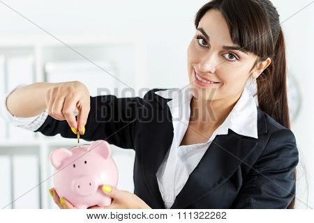 Happy Beautiful Woman Putting Pin Money Coins Into Pink Piggybank