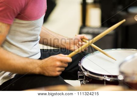 music, people, musical instruments and entertainment concept - male musician playing cymbals and pointing drumstick to you at music store