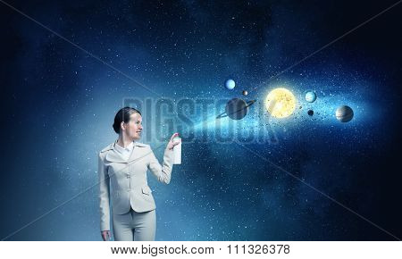 Young businesswoman spraying space planets from aerosol balloon