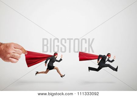 two superheroes fast running but big mans hand holding red cloak of superwoman over light grey background