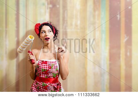 Young beautiful amazed woman holding paint roller