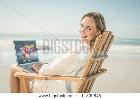 Gorgeous blonde sitting on deck chair using laptop on beach against online shopping concept