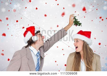 Man wearing Santa hat and holding mistletoe with surprised woman looking at him against snowflake pattern