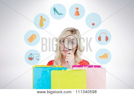 Fair-haired woman looking through a magnifying glass against gift bags