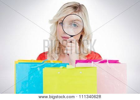 Fair-haired woman looking through a magnifying glass against grey background