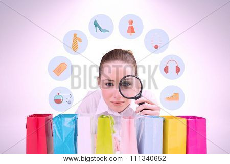 Businesswoman typing and looking through magnifying glass against gift bag