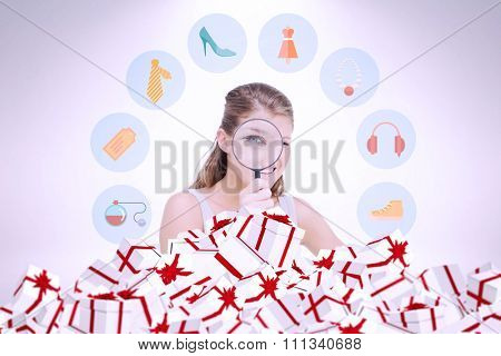 Woman looking through a magnifying glass against christmas presents