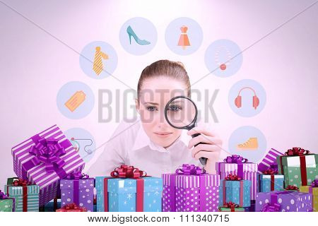 Businesswoman typing and looking through magnifying glass against many colourful christmas gift boxes