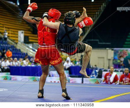 JAKARTA, INDONESIA - NOVEMBER 17, 2015: Reyel Bowen of Bermuda (red) fights Sandor Molnar of Hungary (black) in the men's 85kg Sanda event at the 13th World Wushu Championship 2015.