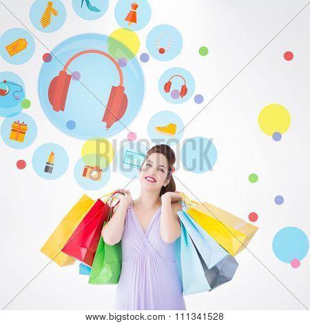 Thoughtful brunette holding shopping bags against dot pattern