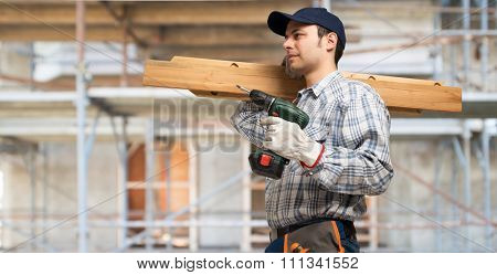 Portrait of a carpenter wood planks and a drill in a construction site