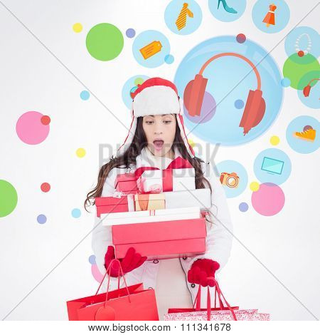Surprised brunette in winter clothes holding many gifts and shopping bags against dot pattern