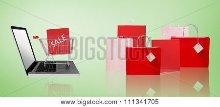 Trolley on laptop with sale bag against green vignette
